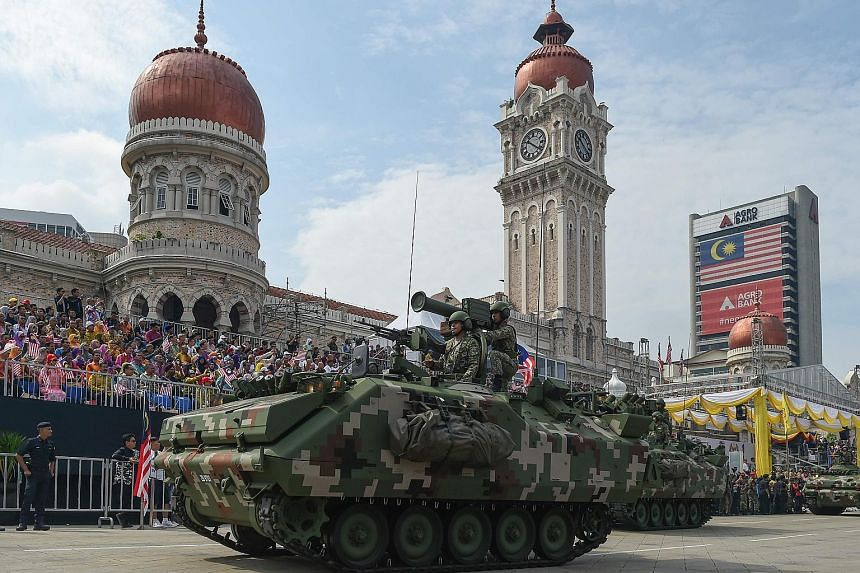 Armoured vehicles rumbling down Kuala Lumpur's Merdeka Square at yesterday's 60th National Day celebrations.