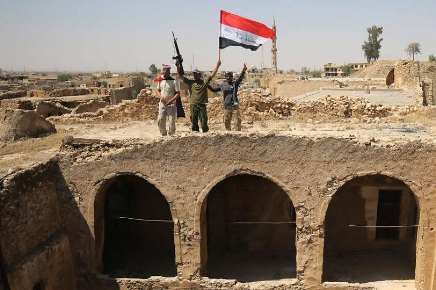 Fighters from the Hashed al-Shaabi (Popular Mobilisation units), backing the Iraqi forces, pose with the Iraqi flag from Tal Afar's Ottoman-era historic citadel on Aug 27, 2017.