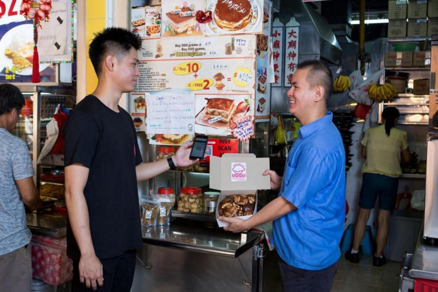 A customer (left) scanning a QR code to pay for muffins at Uggli Muffin stall at Toa Payoh.