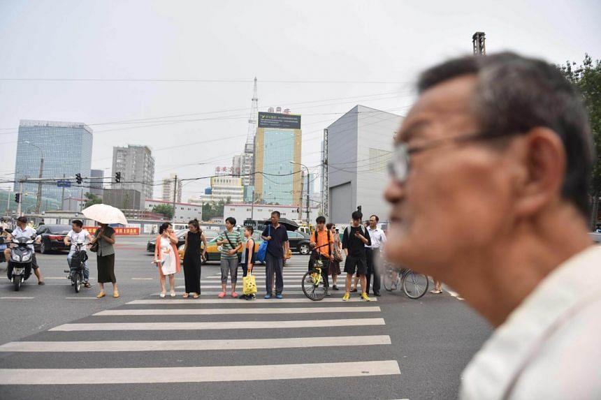 People cross an intersection in Beijing on July 20, 2017.