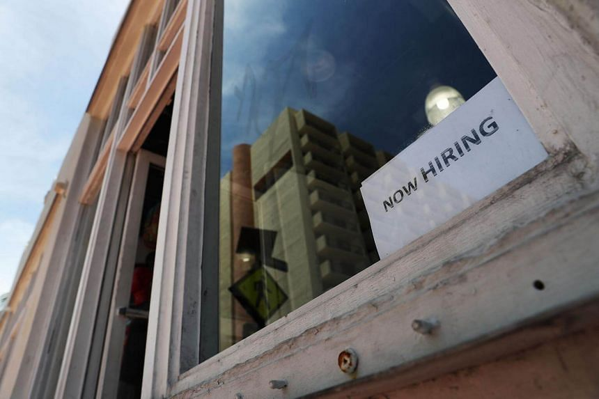 "A ""now hiring"" sign in a window of a business in Miami, Florida on July 6, 2017."