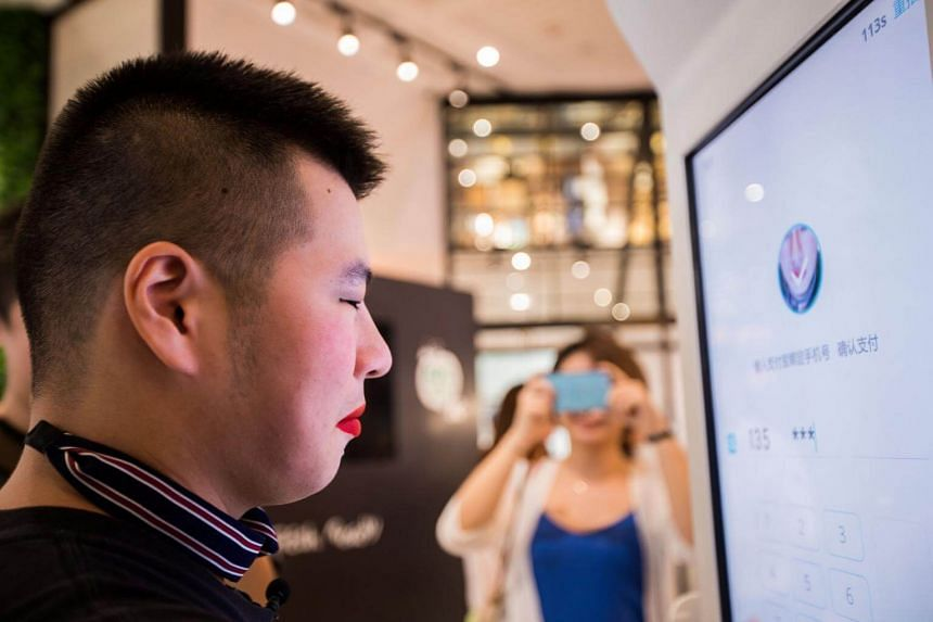 A customer tries Alipay's facial recognition payment solution Smile to Pay at KFC's new KPRO restaurant in Hangzhou, Zhejiang province, China Sep 1, 2017.