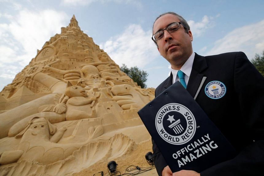 Jack Brockbank, the official judge of Guinness World Records stands next to the world's highest sandcastle (16.68 metres) in Duisburg, western Germany, Sep 1, 2017.