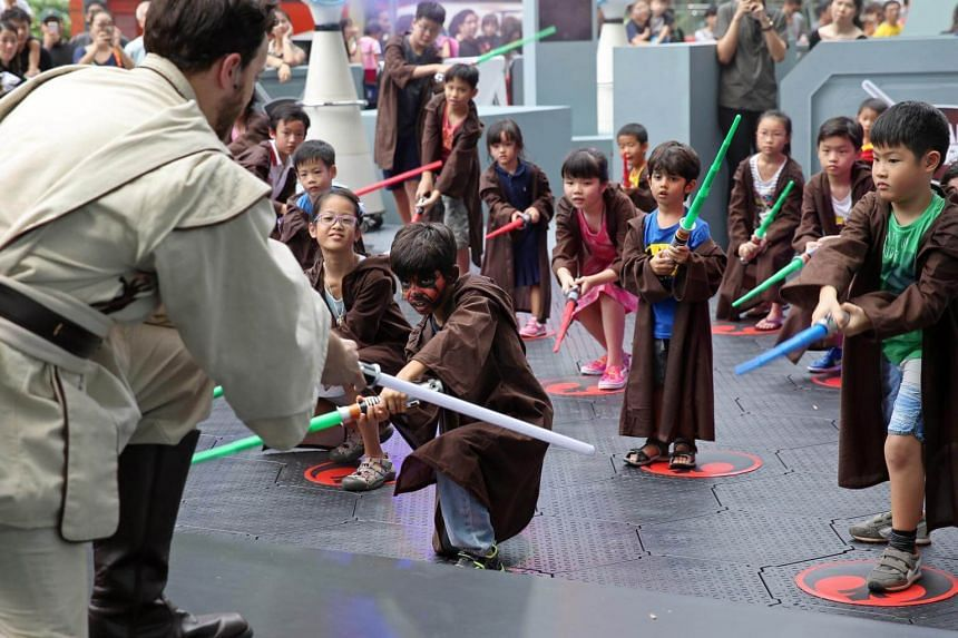 Vihaan Chopra (centre), seven, and his younger brother Vinayak Chopra (centre right), four, take part in a Padawan training session outside Ion Orchard, on Sept 1, 2017.