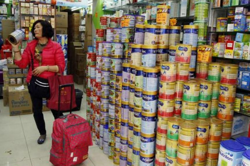 A Chinese visitor asks for the price of a canned infant formula at a store.