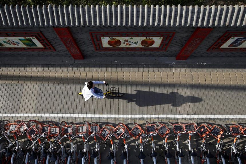 A woman rides an Ofo shared bicycle past a row of Mobike bicycles in Beijing on April 21, 2017.
