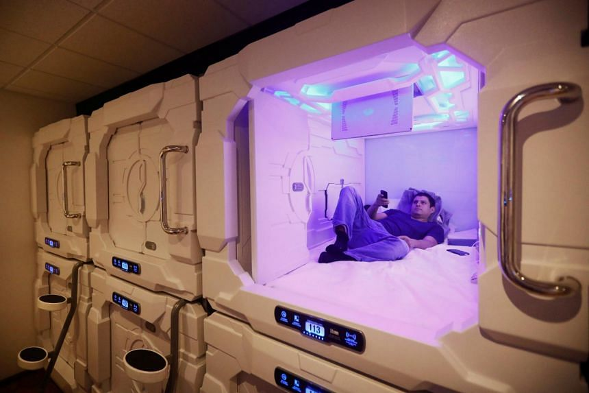 A guest watches television inside his room in Mexico's first capsule hotel at Benito Juarez International airport in Mexico City, on Aug 30, 2017.
