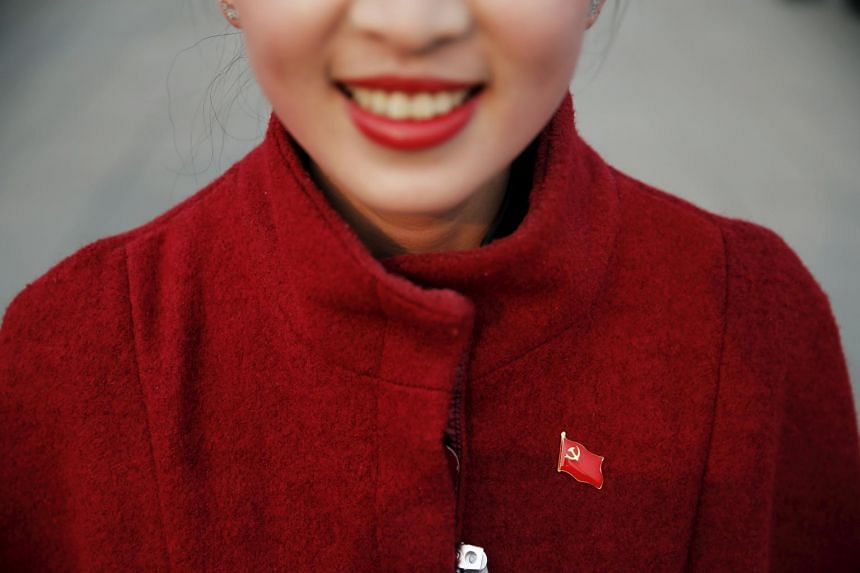 A hostess wears a pin of China's Communist Party flag ahead of the closing ceremony of National People's Congress (NPC) in Beijing.