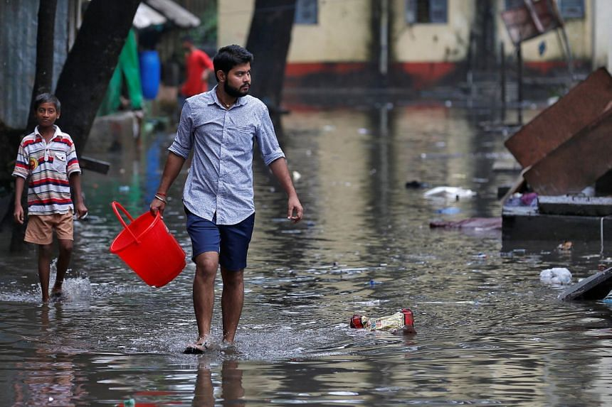 A man carrying a bucket walks through a water-logged neighbourhood in Mumbai, India, on Aug 30, 2017.