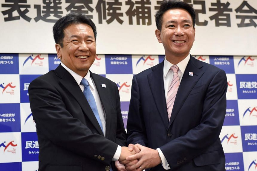 Presidential candidates for the Democratic Party Yukio Edano (left), a former chief Cabinet secretary, and Seiji Maehara, a former foreign minister, shake hands following their press conference at the party headquarters in Tokyo on Aug 21, 2017.