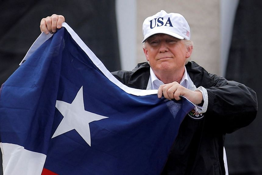 Trump holds a Texas flag during a trip to the US stste in the aftermath of storm Harvey, Aug 29, 2017.