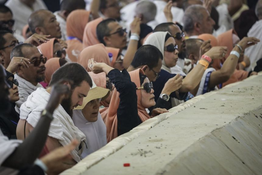 Muslim worshippers throw pebbles as part on the symbolic stoning ritual at the Jamarat Bridge.