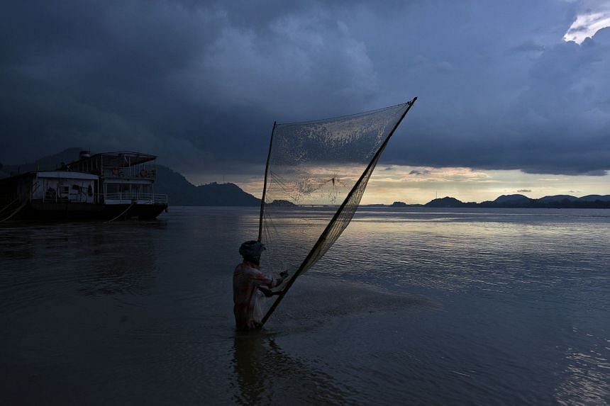 A man catches fish at the banks of the Brahmaputra river in Guwahati, India, on Aug 28, 2017.