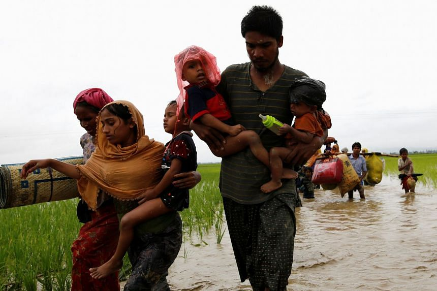 Rohingya refugees wade across water after travelling over the Bangladesh-Myanmar border, Sept 1, 2017.