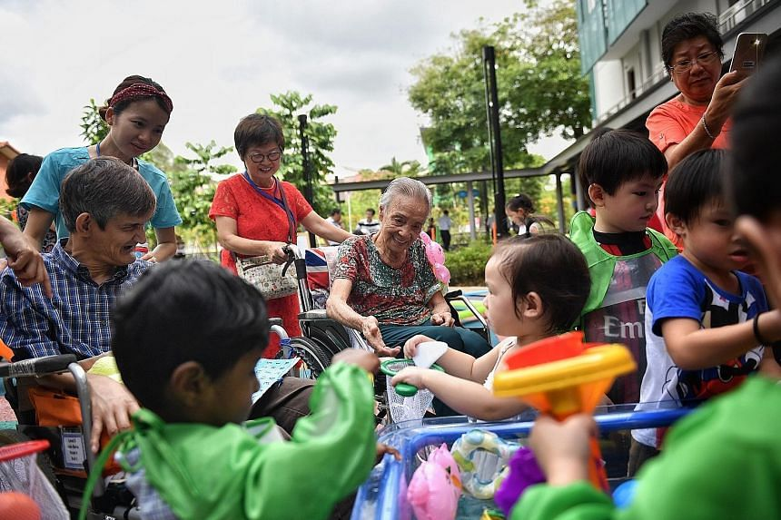 Nursing home residents and children interact under supervision at the inter- generational playground of St Joseph's Home.