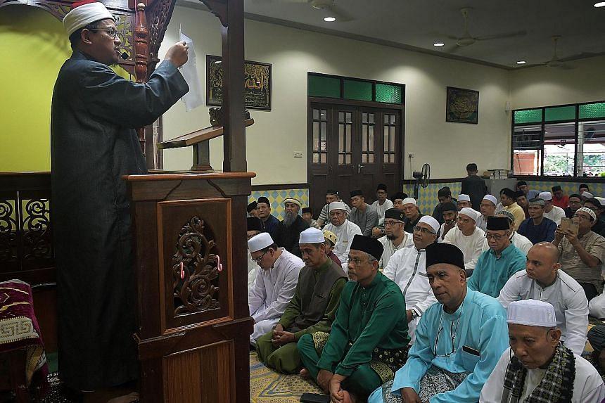 Mufti Mohamed Fatris Bakaram leading morning prayers at Masjid Petempatan Melayu yesterday. Among the congregants attending was Minister Masagos Zulkifli (front row, third from right).