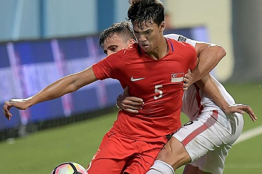 Lions forward Ikhsan Fandi and Hong Kong's Helio Goncalves tussle for the ball during the football friendly at the Jalan Besar Stadium on Thursday. The 18-year-old won his first cap as a substitute and will earn plenty more, should he continue on the