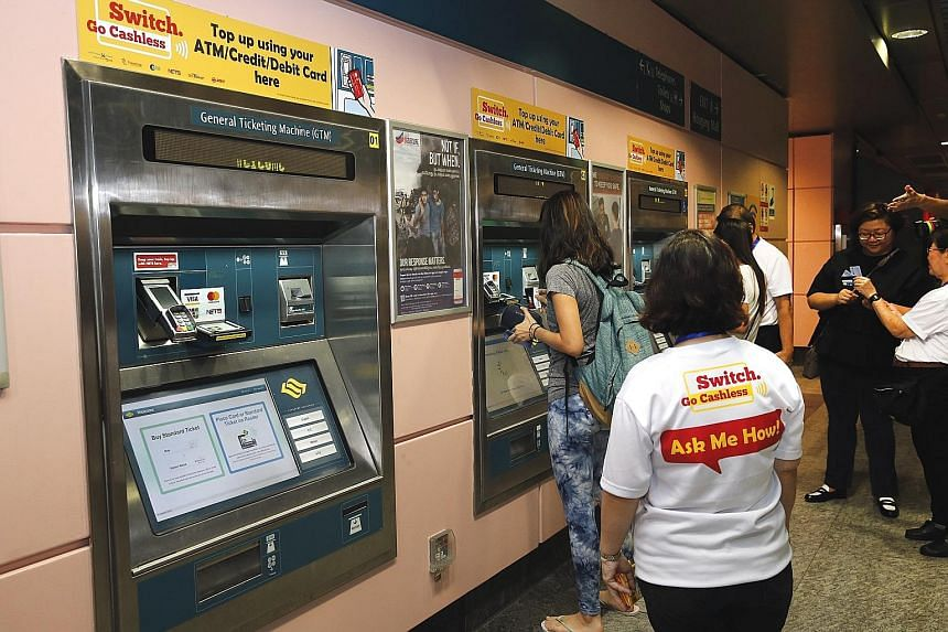 A service agent standing by to guide commuters in topping up their ez-link cards using ticketing machines at Hougang MRT station yesterday.