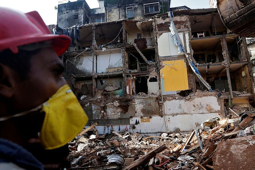 A rescue worker searching for survivors yesterday at the site of the building collapse in Mumbai. The 117-year-old building came crashing down on Thursday after days of heavy rain.