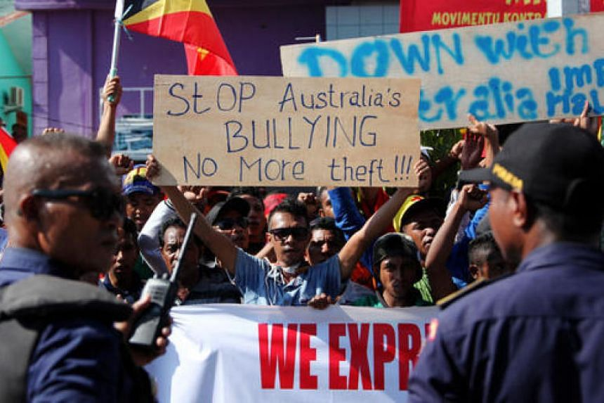 Timorese students hold placards during a protest outside the Australian embassy in Dili, Timor Leste on March 22, 2016. Hundreds of students demanded a dialoque between Australian and Timor Leste governments to resolve their boundary dispute.
