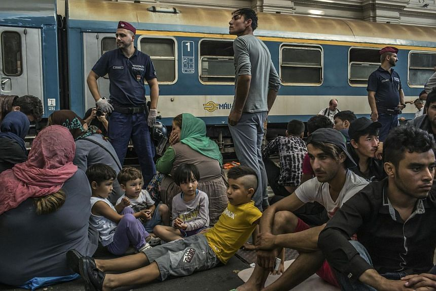 A group of migrants wait to take a train to Germany, at the Keleti station in Budapest, Hungary, Sept. 3, 2015.