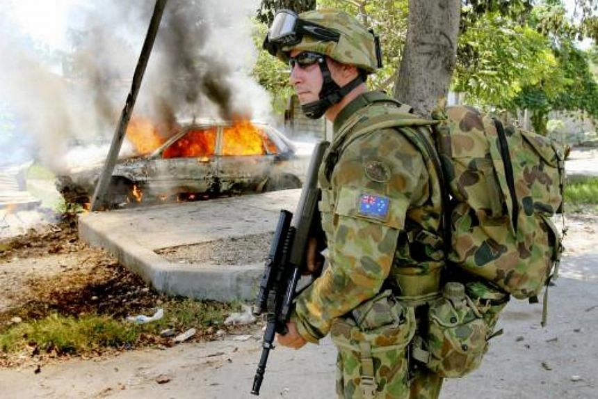 An Australian patrolling past a burning car as rival gangs clash in flashpoints around the captial of Dili on May 30, 2006.