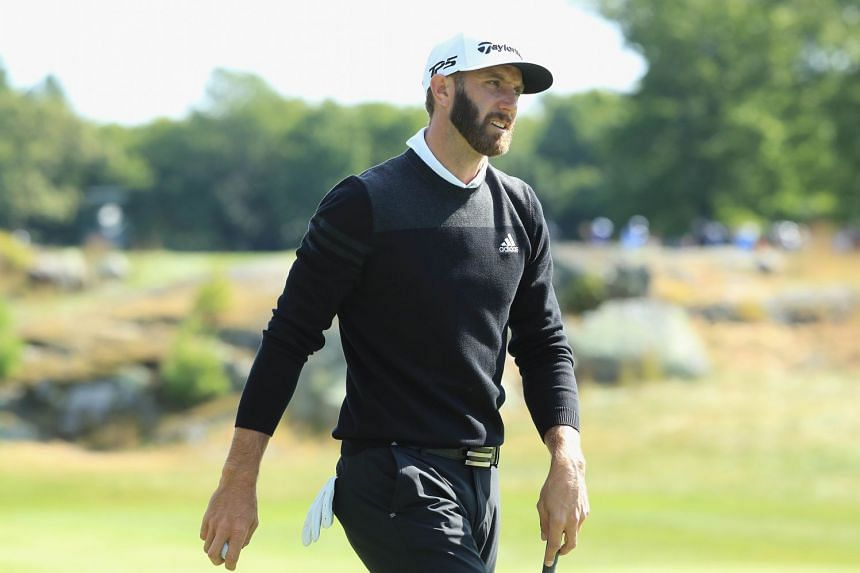 Dustin Johnson walks on the 12th green during round one.