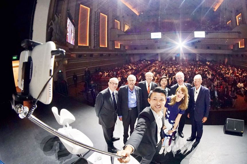 Guest of honour Baey Yam Keng, Parliamentary Secretary for Culture, Community and Youth, taking a wefie with (from left) Mr Paul Donovan, chief global economist, UBS Wealth Management; Nobel laureates Peter A. Diamond and Robert Merton; Ms Tracey Woo