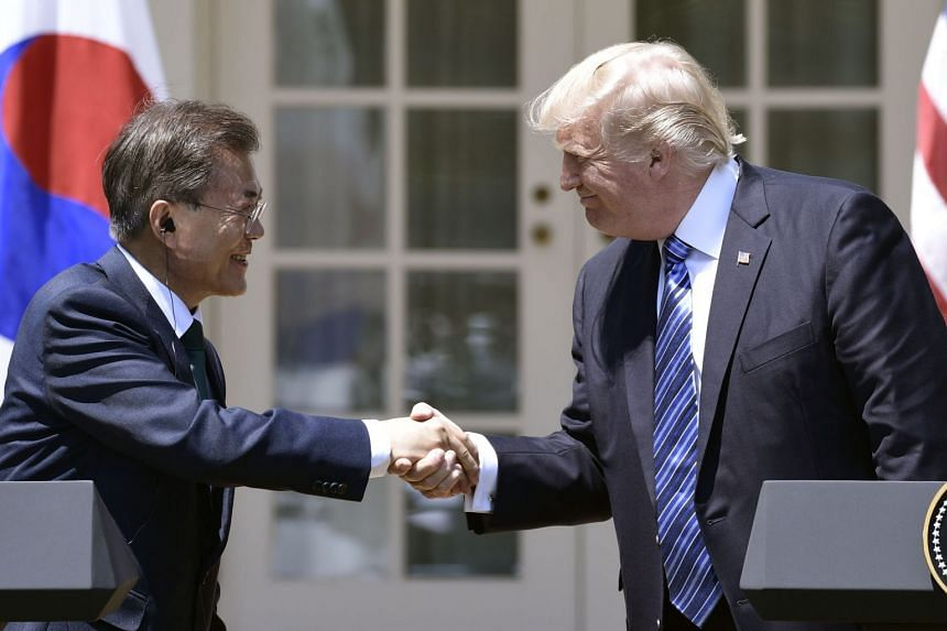 US President Donald Trump shaking hands with South Korean President Moon Jae In during a joint press conference in the Rose Garden at the White House in Washington, DC on  June 30, 2017.