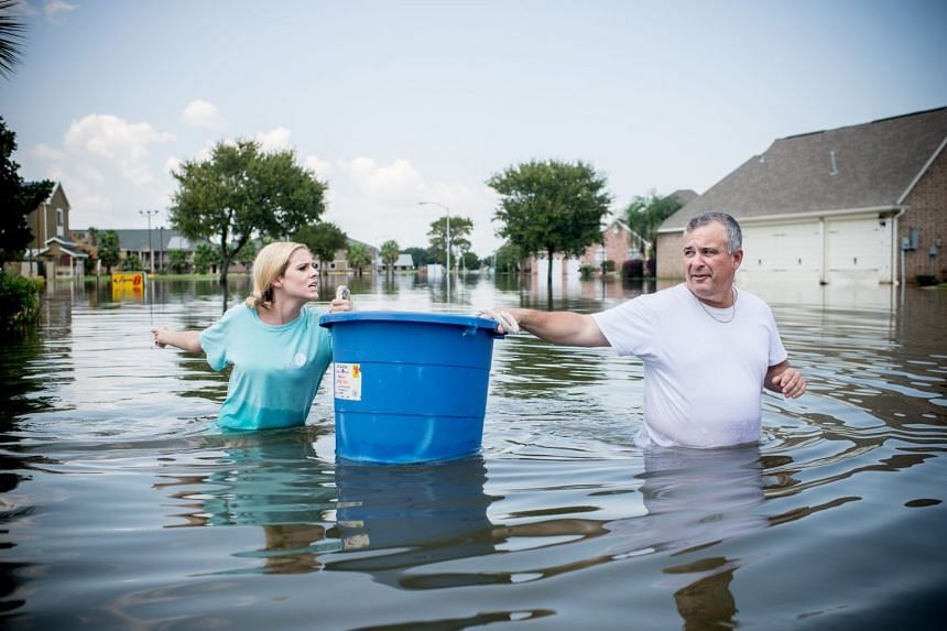 Jenna Fountain and her father Kevin carry a bucket to try to recover items from their flooded Texas home.