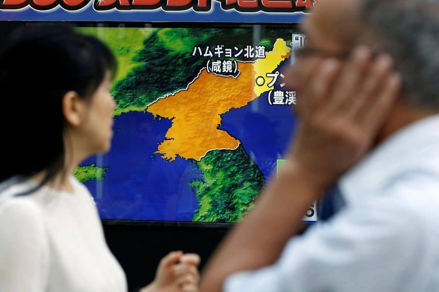 People walking past a screen showing a news report on North Korea's latest nuclear test, in Tokyo on Sept 3, 2017.