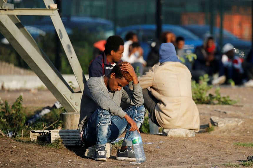 """Migrants wait for food distribution near the former """"jungle"""" in Calais, France, Aug 23, 2017."""