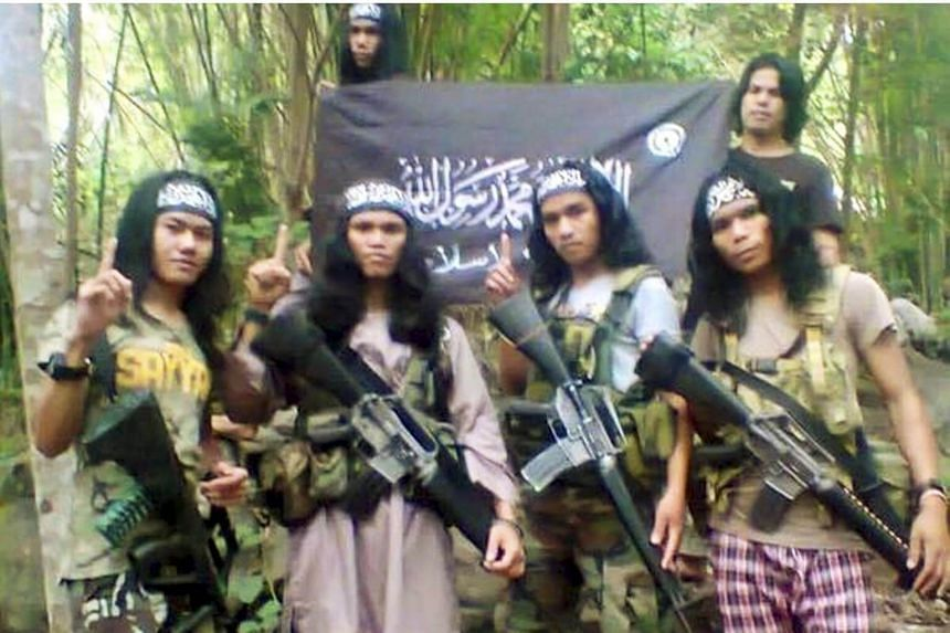 Suspected Abu Sayyaf member Abu Asrie (extreme left) was one of eight men who were arrested in Kuala Lumpur on Aug 30.