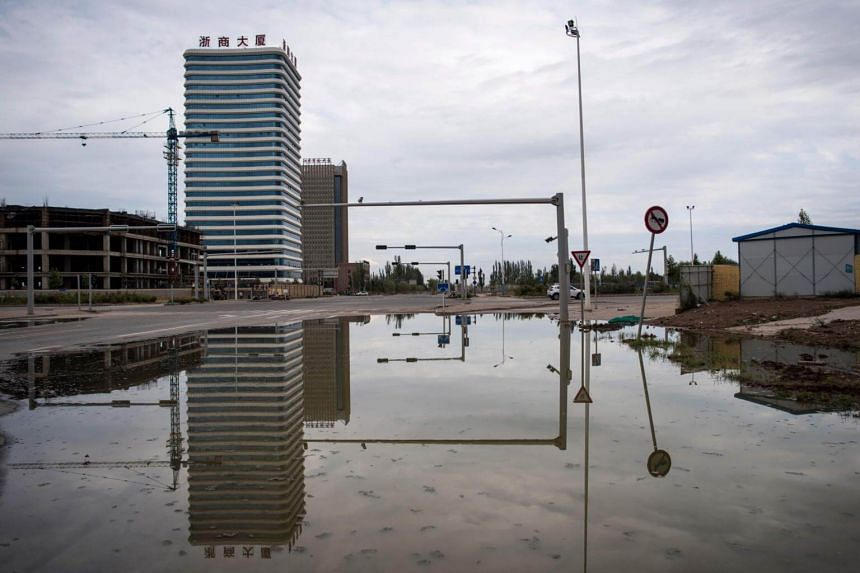 An empty road runs along a construction site at a development called Shenzhen City, on the outskirts of Kashgar, Xinjiang province, on June 25, 2017.