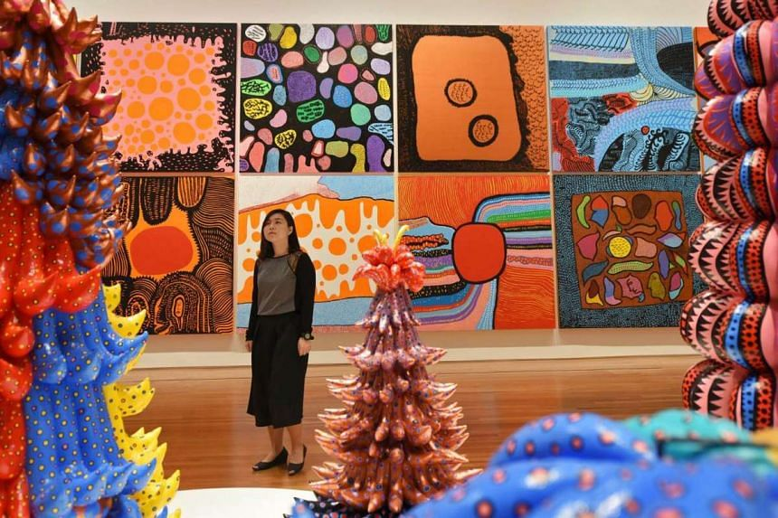 A gallery staff looks on at the soft sculptures, with some of Kusama's newer works in the background, including the piece Life Is The Heart Of A Rainbow, produced just this year.
