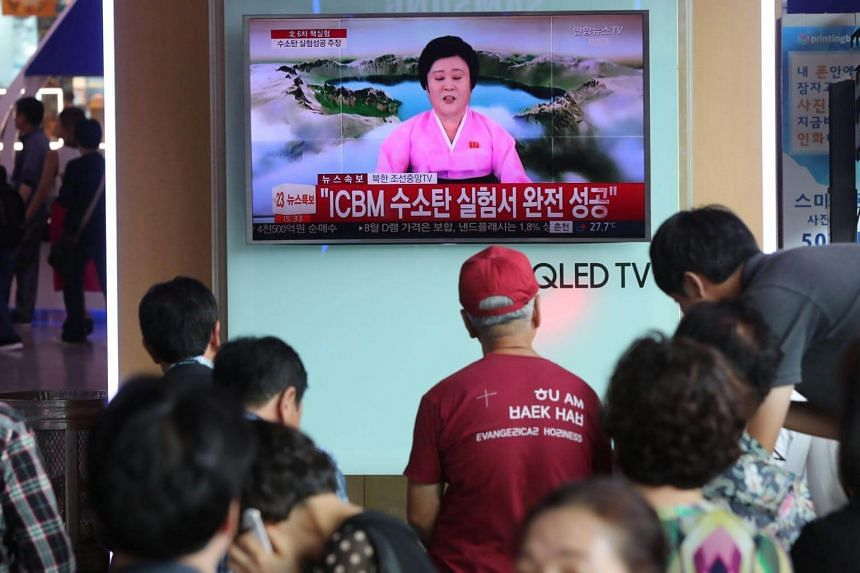People watching a news programme on North Korea's latest nuclear test, in a train station in Seoul on Sept 3, 2017.