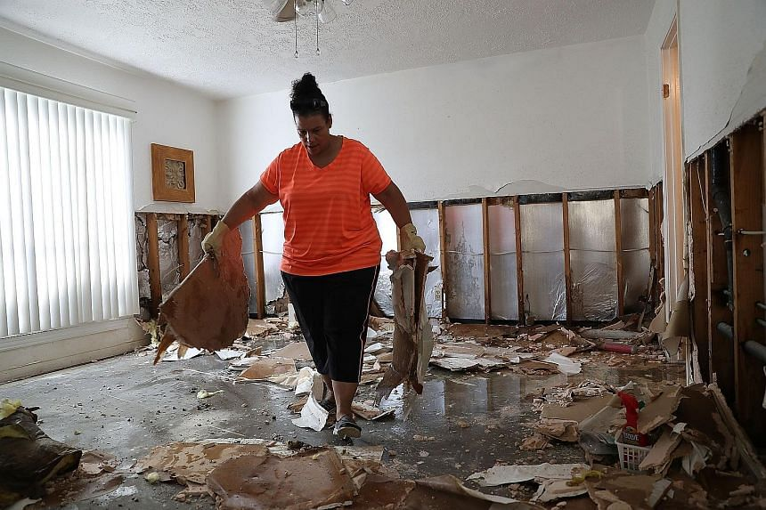 """A resident cleaning her home in Houston, Texas, yesterday. Houston Mayor Sylvester Turner said most of the city was """"now dry""""."""