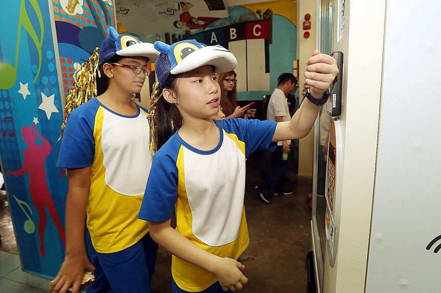Pupil Vernice Lim, 11, using her smartwatch at a vending machine to pay for a drink at Admiralty Primary. The watch is part of the POSB Smart Buddy programme, which aims to help students learn how to save and manage their allowances.