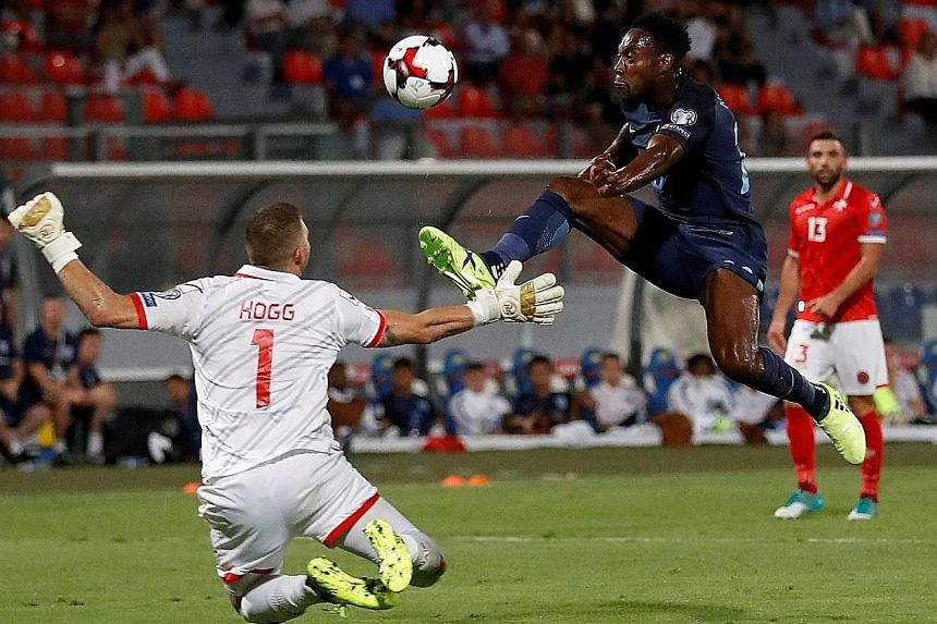 England's Danny Welbeck lifting the ball over Malta goalkeeper Andrew Hogg in stoppage time for his side's third goal. The late flurry of goals added gloss to the 4-0 scoreline which was not as one-sided as it appeared, with three England goals comin
