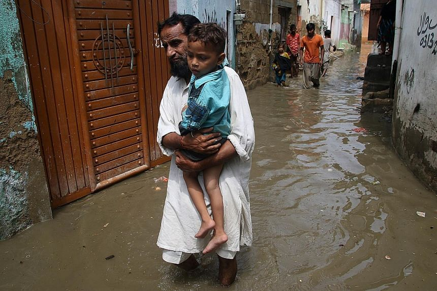 People making their way through a flooded street in Karachi, Pakistan, on Friday. At least 23 people have died in rain-related incidents, mostly due to electrocution, in Karachi in the past two days. India, Nepal and Bangladesh have also endured floo