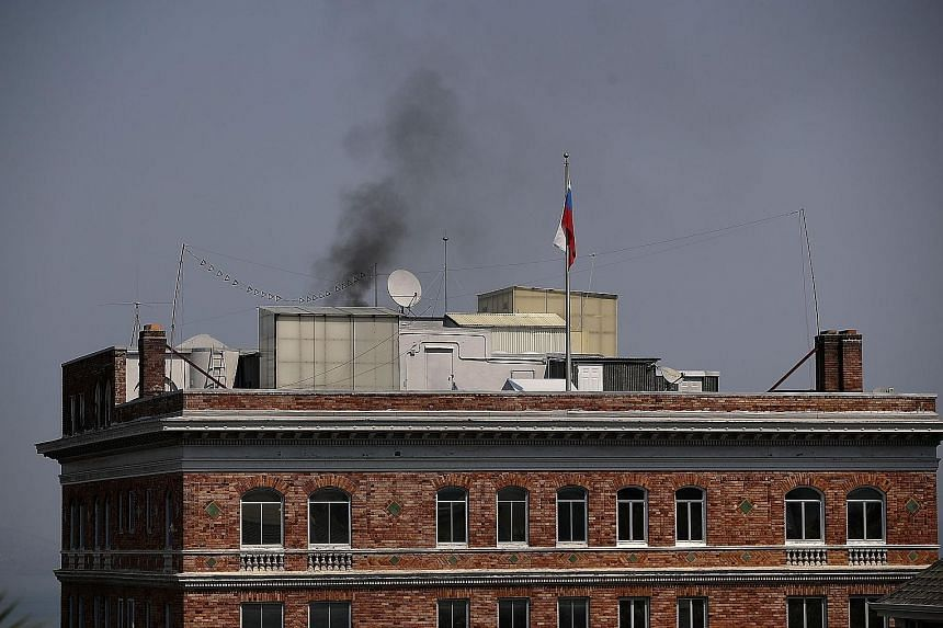 Black smoke billowing from a chimney on top of the Russian consulate in San Francisco, California, on Friday. A conspiracy theory suggests the Russians were burning documents ahead of a search of the building.