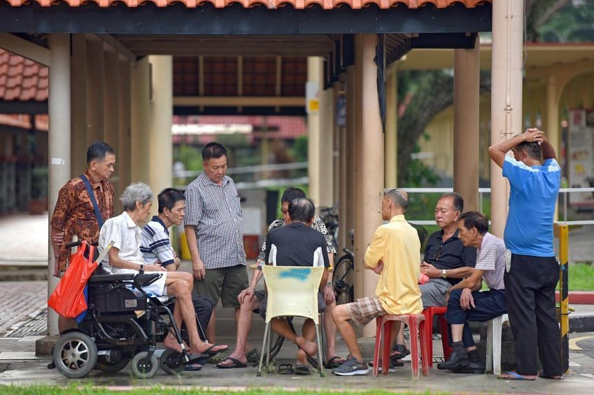 A group of elderly men watching a game of chess at Toa Payoh Central.