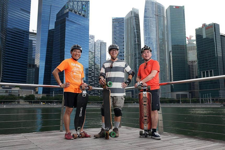 (Left to right) Raymond Tan, 53, and John Cheng, 58, and Simon Lee, 50, with their long boards.
