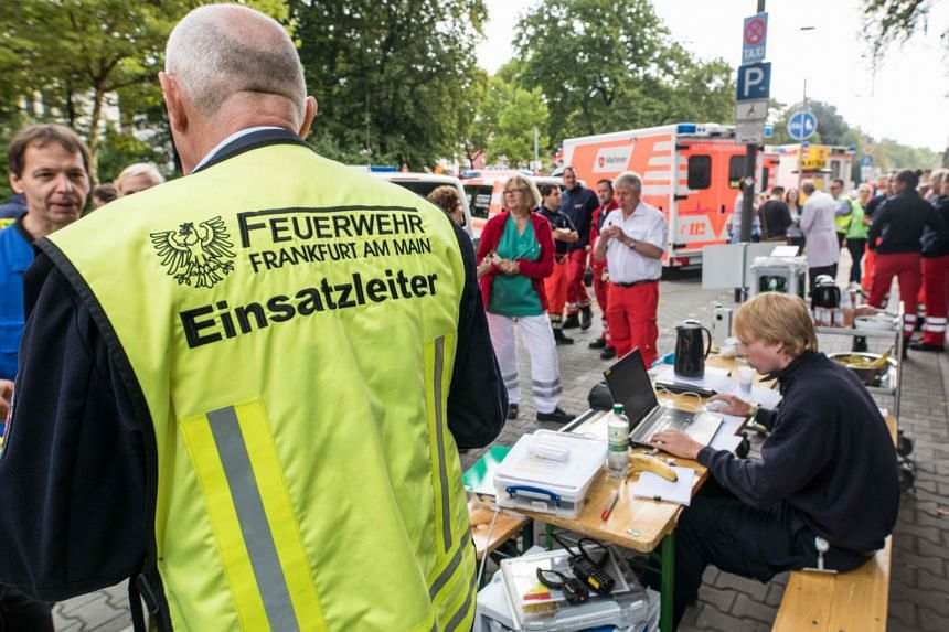 People help move patients from Frankfurt's Buergerhospital clinic,  to another hospital, Sept 2, 2017.