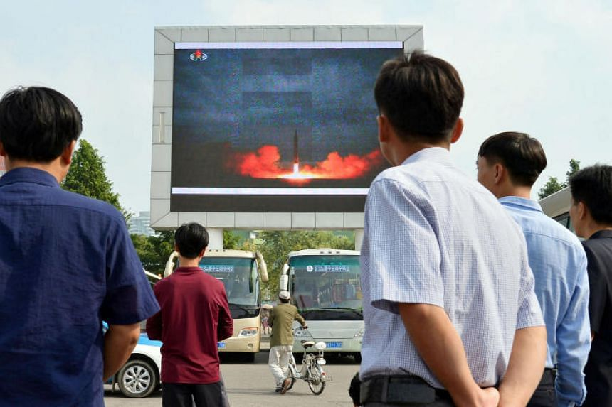 North Koreans watch a news report showing North Korea's Hwasong-12 intermediate-range ballistic missile launch on a electronic screen in Pyongyang.