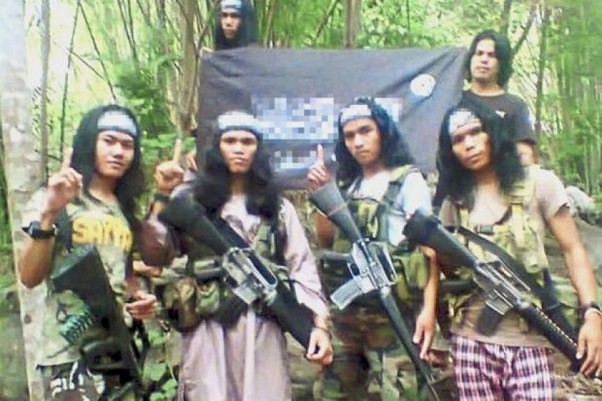 Armed and dangerous: Abu Asrie (left) in an undated picture taken on the Basilan Island in southern Philippines. The others in the photo are believed to be gunmen in the Philippines.