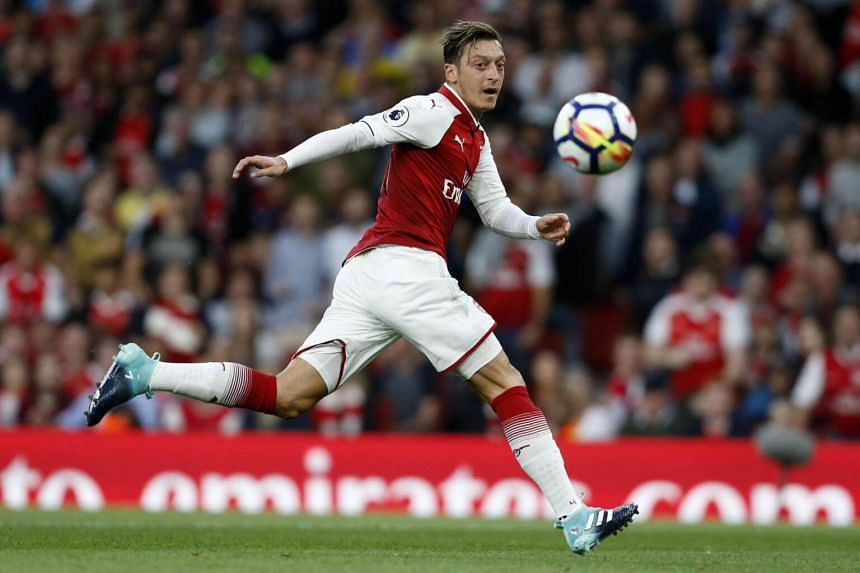 Arsenal's German midfielder Mesut Ozil runs with the ball during the English Premier League football match between Arsenal and Leicester City at the Emirates Stadium in London on Aug 11, 2017.