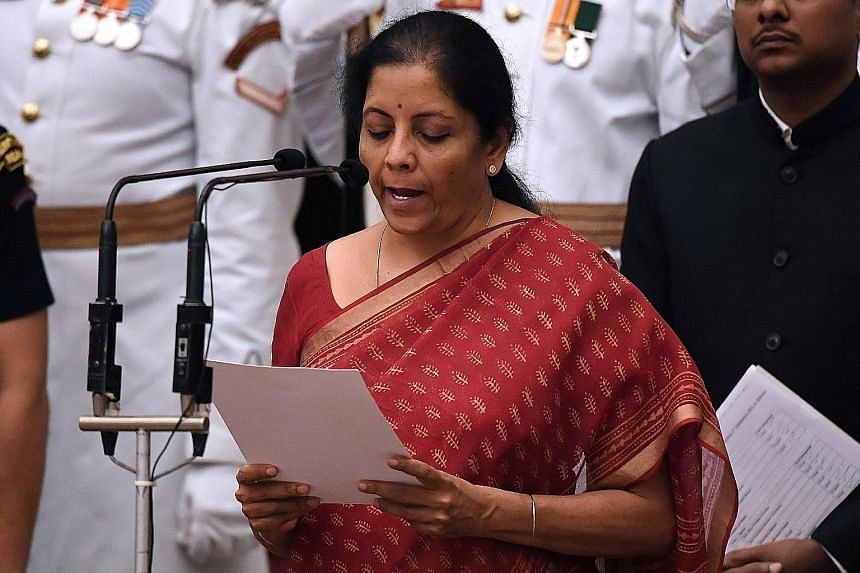 India's new Defence Minister Nirmala Sitharaman taking the oath during the swearing-in ceremony of new ministers at the Presidential Palace in New Delhi yesterday.
