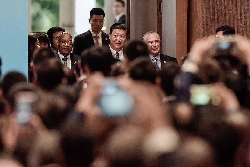"""Chinese President Xi Jinping, flanked by South African President Jacob Zuma and Brazilian President Michel Temer, at the opening ceremony of the Brics Business Forum in Xiamen yesterday. Mr Xi said the bloc should """"promote the Brics-Plus approach to"""
