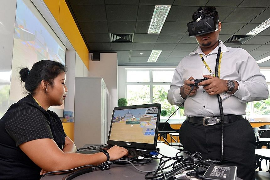 ITE College Central students Noor Rashikin Mohamed Rashid and Lesalan Bathmanathan demonstrating how they use virtual reality to step into different pre-school environments and learn to scan these places for signs of danger.